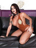 Luana Aquylla is a bodacious TS beauty with a plump booty and massive tits. The trans hottie models a skintight swimsuit and sexy heels, teasing and stripping to start. Luana takes a seat on the couch, soon pulling out her diamond-hard rod for a kinky mas